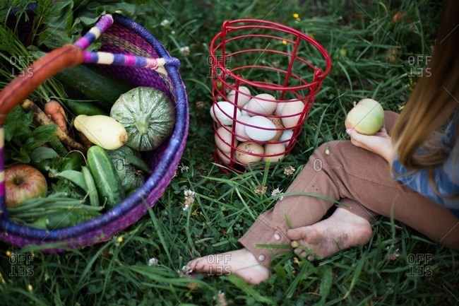 Girl sitting outside next to a basket of eggs and a basket of fruits and veggies