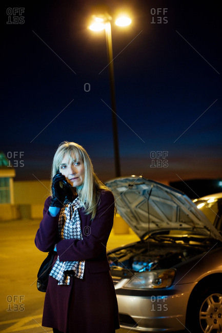 Woman on cellphone with broken down car