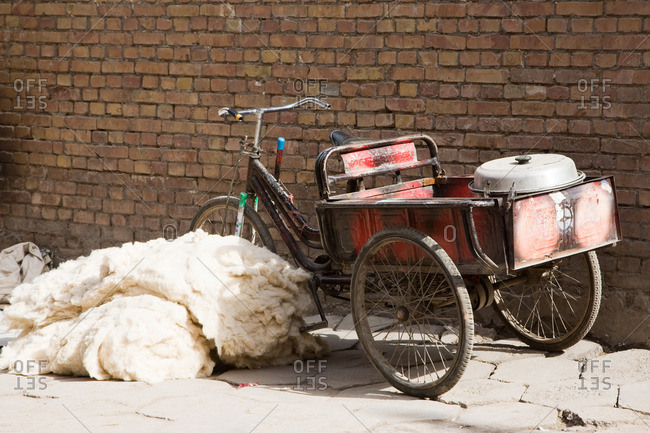 Bicycle next to pile of wool on footpath