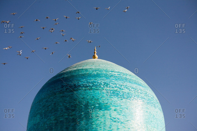Flock of birds flying over cupola of mosque