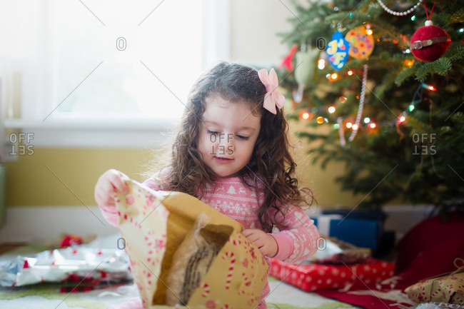 Close up of a little girl opening a gift on Christmas morning