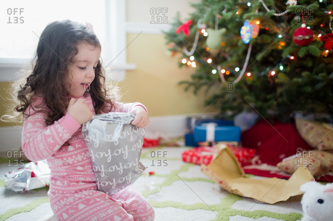 Little girl unwrapping a toy on Christmas morning