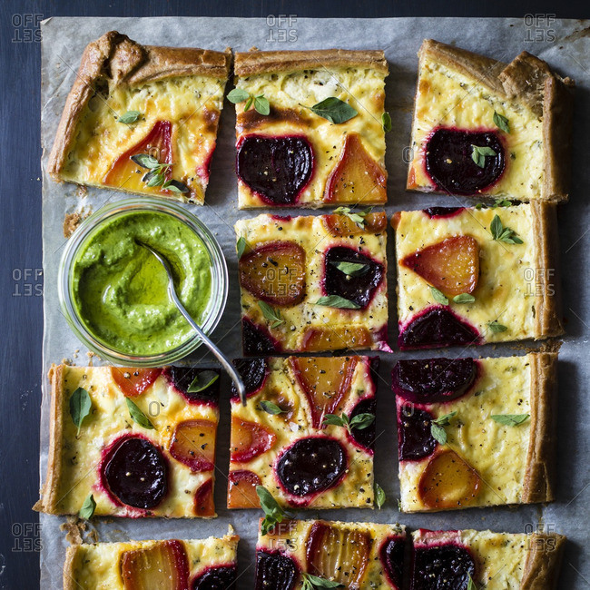 Beetroot ricotta cheese tart with beet greens pesto sliced into squares