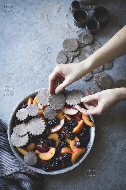 A hand placing dough shapes on a blackberry peach buckwheat pandowdy