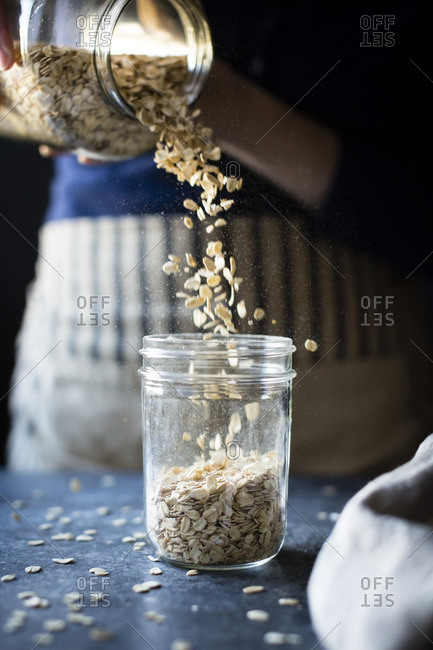 A woman pouring oats into a jar