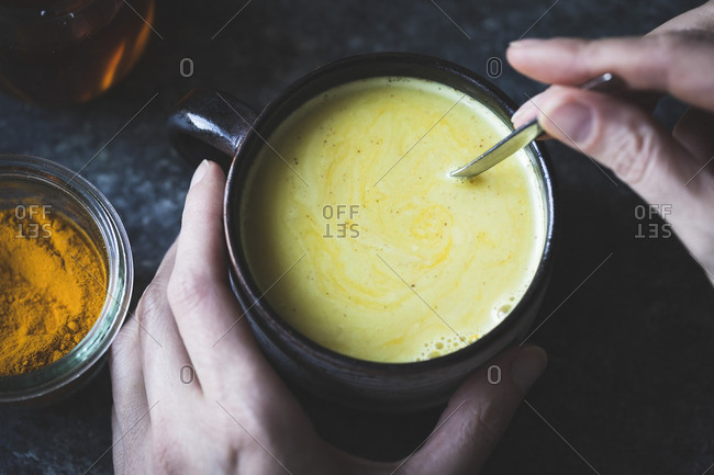 Golden Milk in a mug - mixed honey, turmeric, ginger, cardamom, and cinnamon