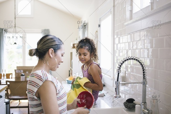Mother and daughter washing dishes together