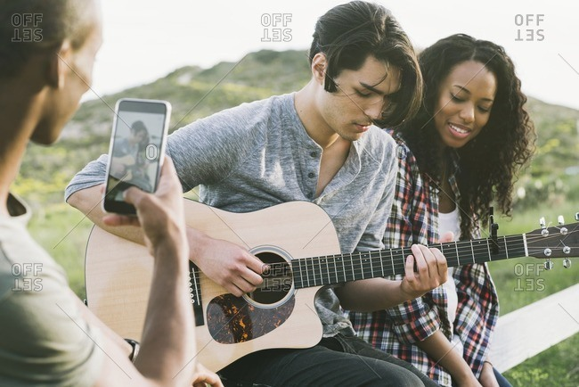 Young man playing guitar while friend takes a picture on his smartphone