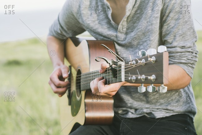 Close up of young man playing an acoustic guitar outside