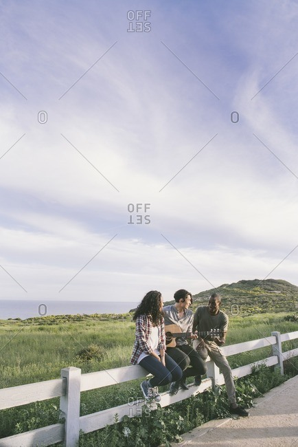 Three friends sitting on a split rail fence near the ocean as one plays guitar