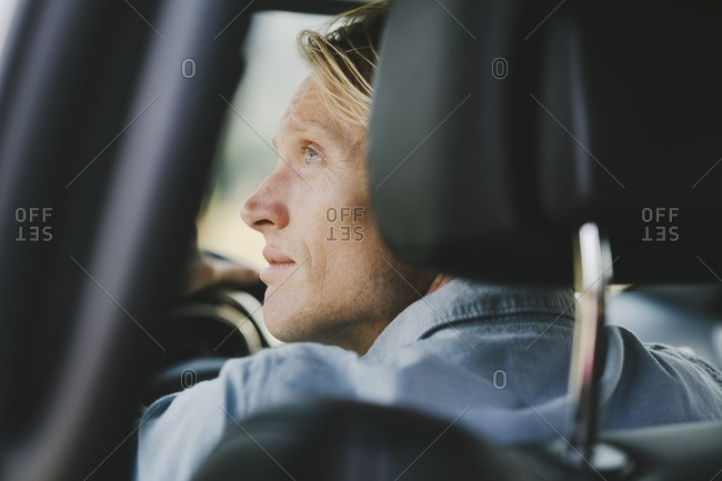 Man in the front seat of a car looking out the window