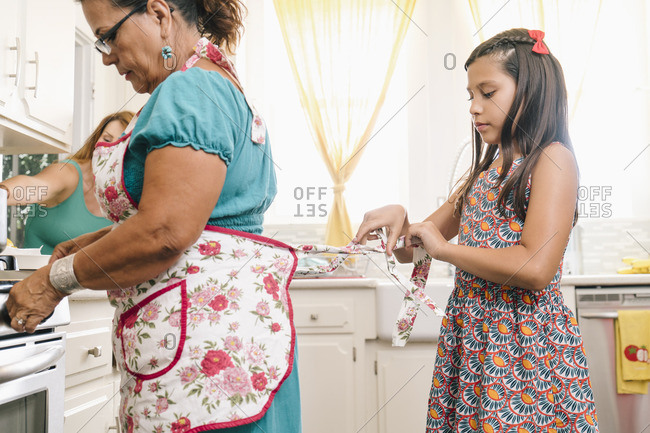 Granddaughter tying grandmother's apron in the kitchen