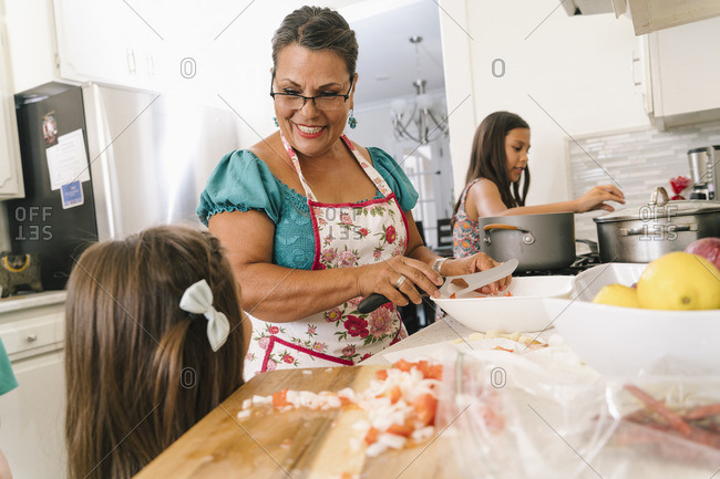 Grandmother and granddaughters preparing meal in the kitchen