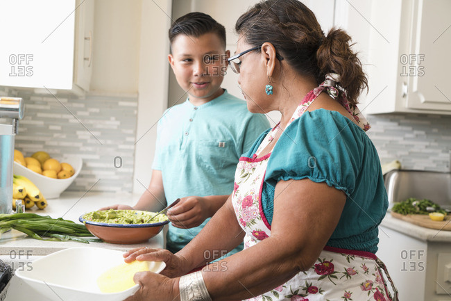 Grandson showing bowl of guacamole to his grandmother