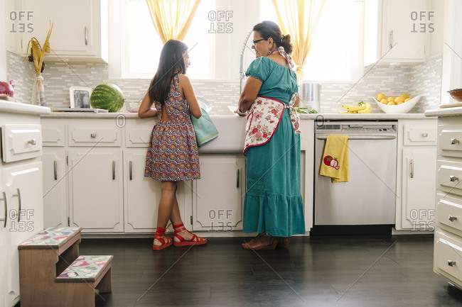 Woman and granddaughter doing dishes at the kitchen sink