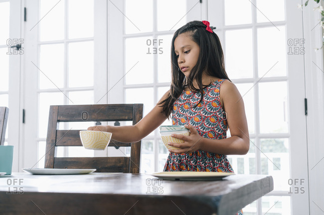 Young girl setting dishes on dining room table