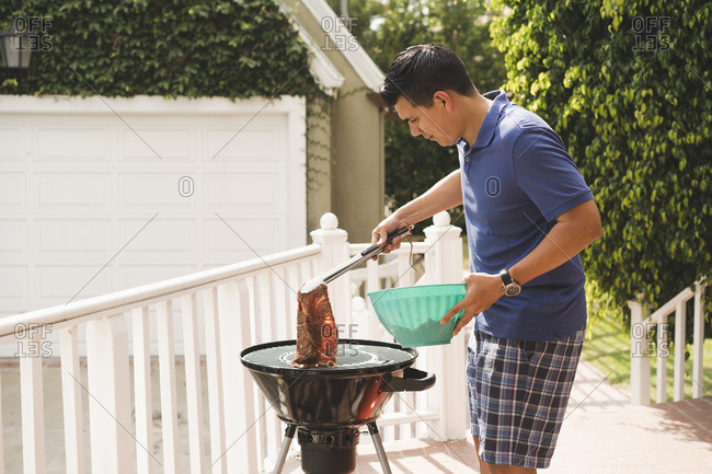 Man grilling meat on a barbeque grill