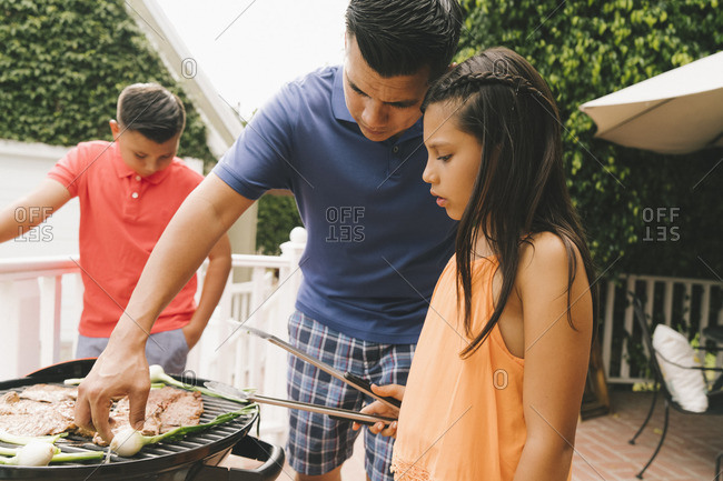 Father and children grilling food on a barbeque grill