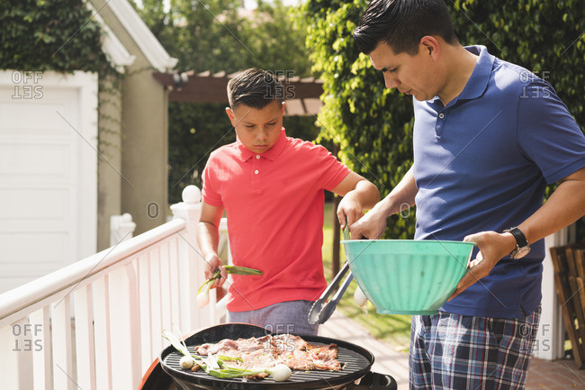 Father and son grilling meat on a barbeque grill