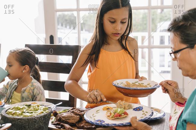 Girl serving her grandmother at dinner