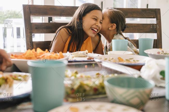 Girls telling secrets at the dinner table