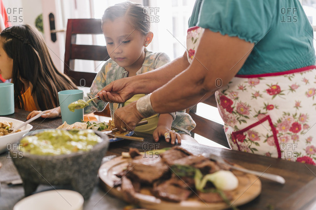 Woman serving guacamole to her granddaughter at dinner