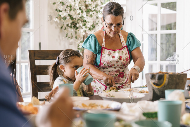 Woman serving food to her granddaughter at dinner