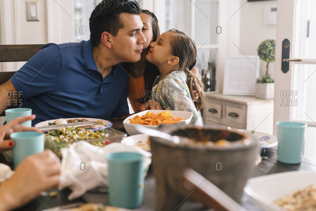 Girls kissing father on his cheek at dinner