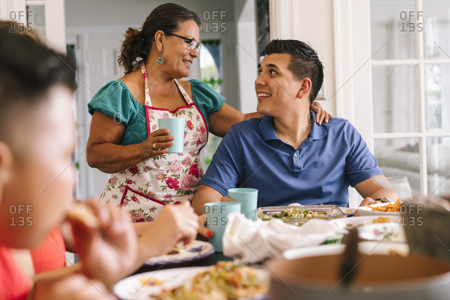 Woman standing with arm around her adult son at dinner