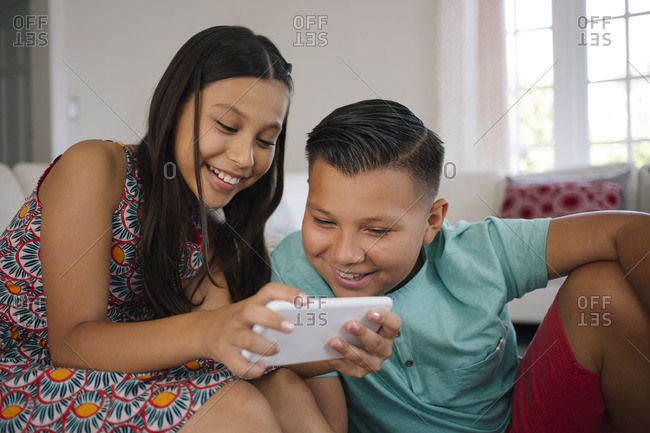 Sister showing brother smartphone