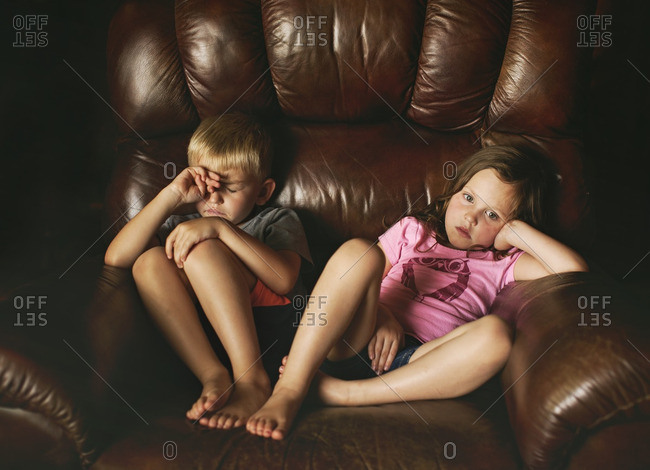 Brother and sister sitting together in a leather easy chair