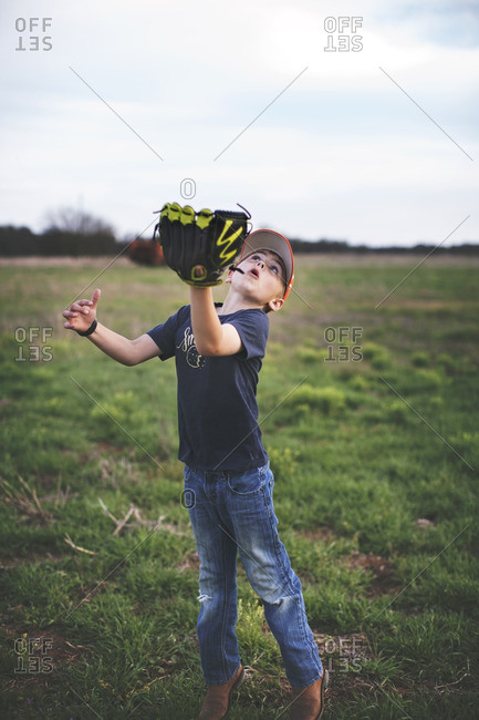 Boy with a catcher's mitt trying to catch a ball in a field