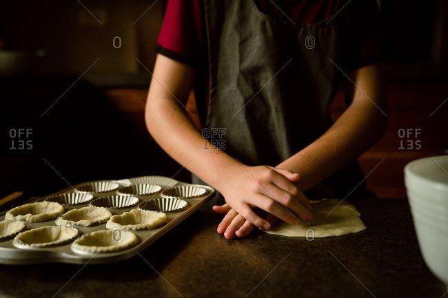 Child preparing crust for homemade tarts