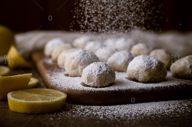 Lemon cookie dough balls being sprinkled with powdered sugar