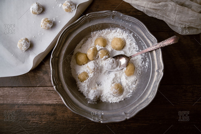 Lemon cookie dough balls being rolled in powdered sugar