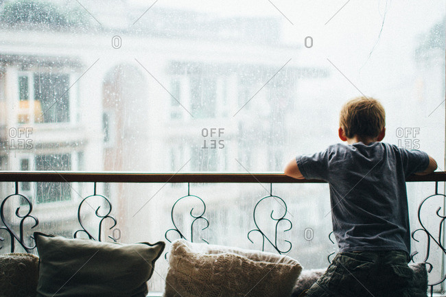 Boy looking out rainy city window