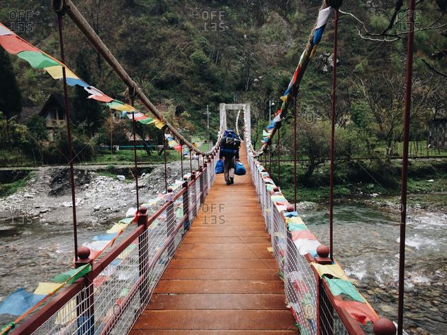 Backpacker crossing rural footbridge