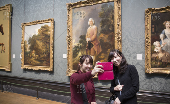 London, England - September 12, 2016: Two women taking a selfie in front of a painting at the National Gallery