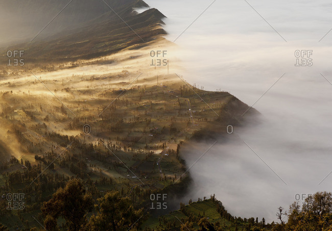 Fog rolling over a mountain at sunrise