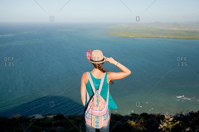 Woman in a hat standing on a cliff overlooking the sea