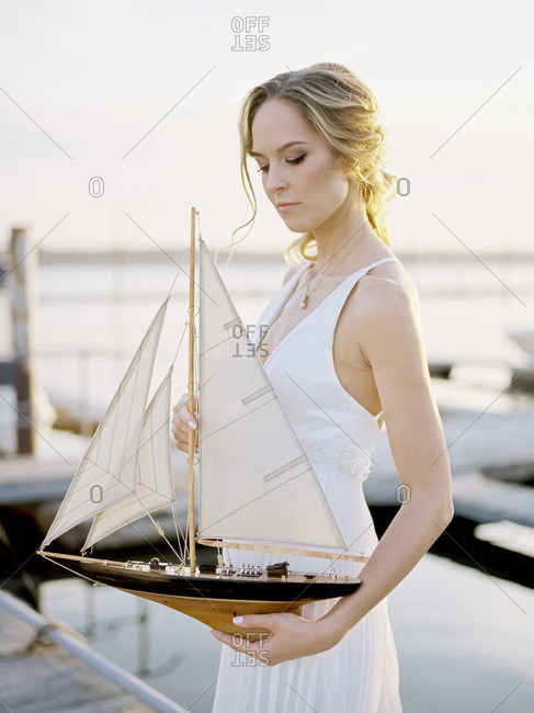 Woman in a white dress holding a model sailboat