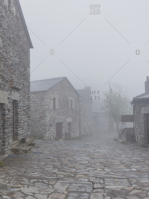 Historic stone buildings on a cobblestone street in the fog