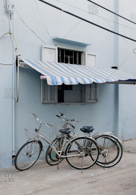 Two bikes parked under a blue striped awning on a blue building