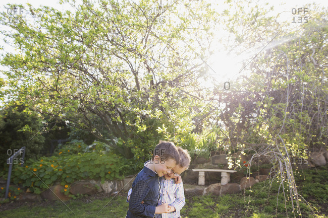 Two boys hugging in sunny setting