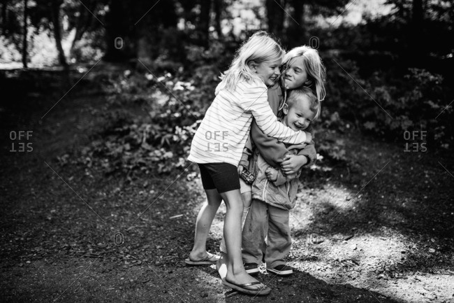 Three siblings on a hiking trail hugging