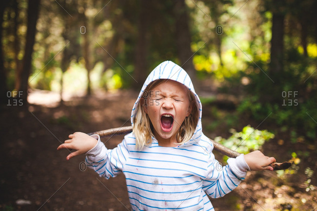 Boy standing on a wooded path yelling