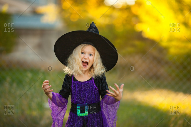Little girl in a witch costume making a scary face