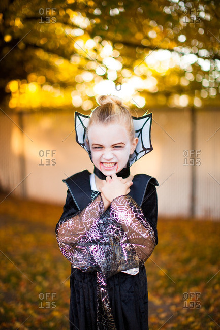 Little girl in a vampire costume making a scary face