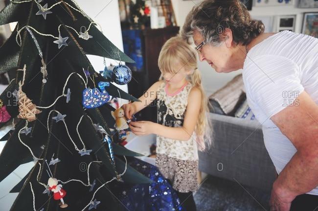 Grandma and girl decorating fake tree
