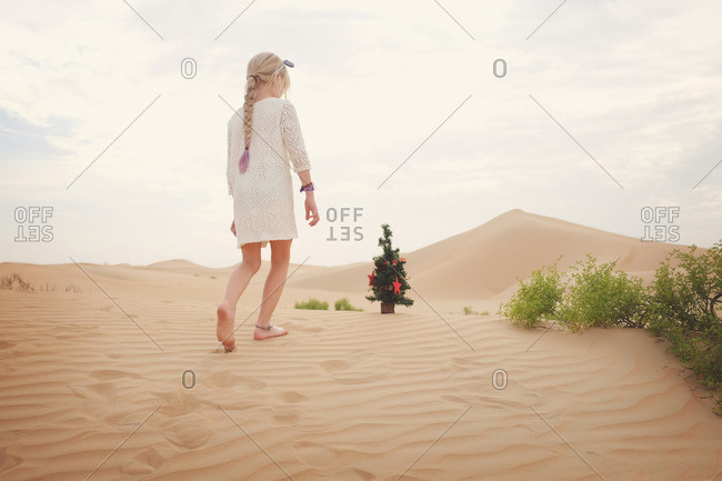 Girl walks in desert at Christmas